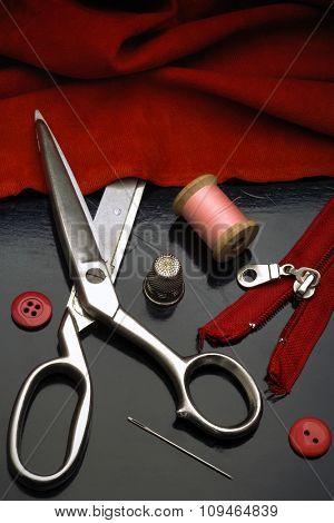 a tailors tools - scissors, needle, thimble, spool of thread, etc. - on black table