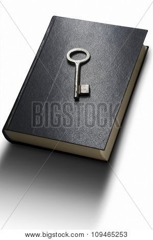 a blad book on white with a silver key on the cover - with clipping path both for the book and the key