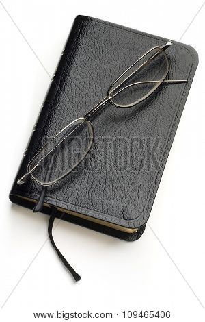 black book on white with a pair of glasses on it