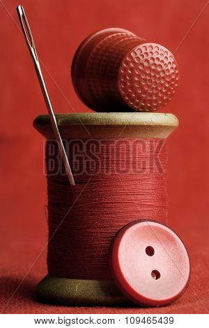 all red sewing items - spool of thread, needle, thimble and a button