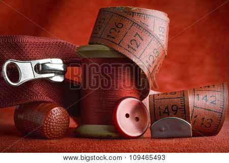all red sewing tools and items - spool of thread, thimble, zipper, measuring tape, button...