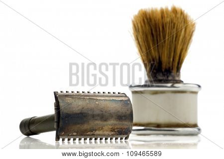 old shaving kit - razor and a shaving brush - on white