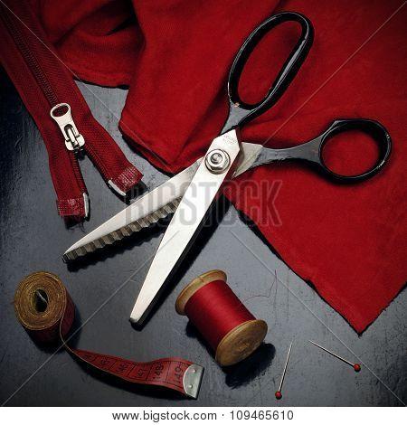 tailor's tools - scissors, spool of thread, measuring tape, pins, zipper, etc...