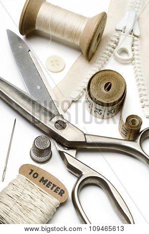 tailor's tools - scissors, spool of thread, needle, thimble, etc. - on white