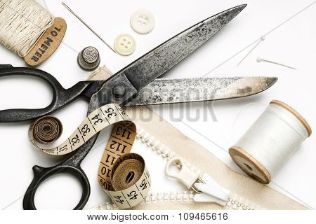 tailor's tools - scissors, spool of thread, pins, zipper, etc. - on white