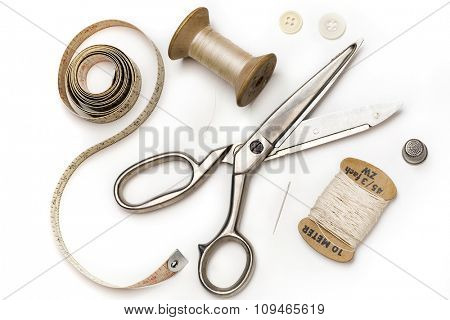 tailor's tools - scissors, measuring tape, thimble, etc. - on white