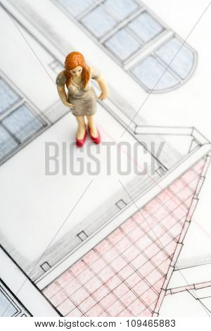 a female figurine standing on her house blueprint (copyright notice: it is a blueprint of my own house - i paid for design)