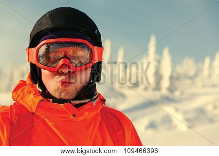 Portrait of a snowboarder in the winter resort in sunglasses mask at ski resort in mountains