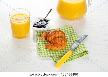 Tasty croissant and orange juice on green checkered napkin