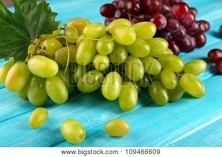 White and red grape on blue wooden background