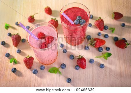 Glasses of berry smoothie on wooden background