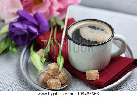 Cup of coffee with flowers on tray, closeup