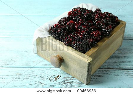 Heap of sweet blackberries in box on table close up