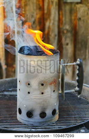 Chimney starter (Charcoal chimney) on top of a BBQ grill
