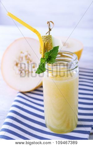 Glass of melon cocktail on white wooden table with striped napkin, closeup