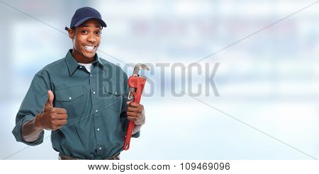 Plumber hands with a pipe wrench over blue banner background.