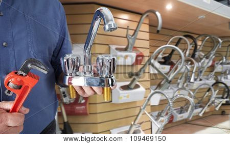 Plumber hands with water tap over plumbing tools background.
