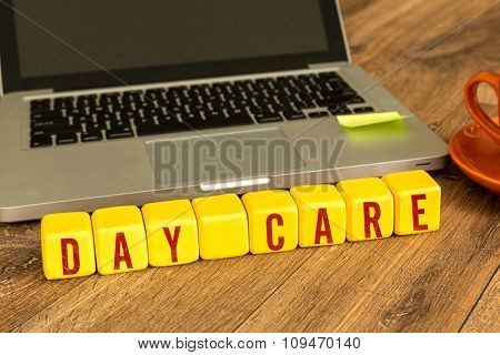 Day Care written on a wooden cube in a office desk