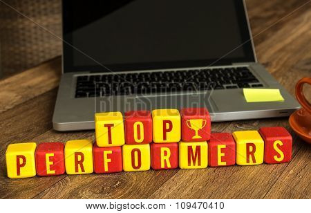 Top Performers written on a wooden cube in a office desk
