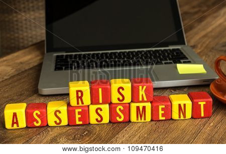Risk Assessment written on a wooden cube in a office desk