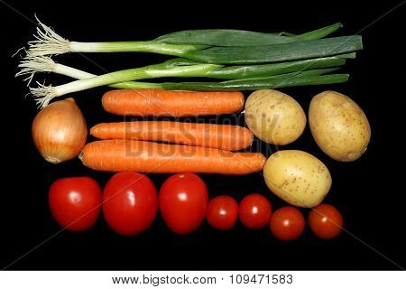 Tomatoes,onions,carrots,potatoes on a black background
