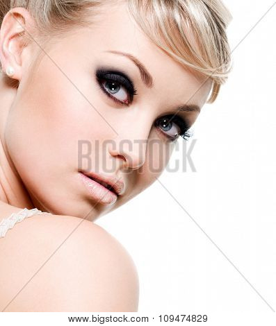 Beautiful sexy woman with black eye make-up. Close-up face isolated on white