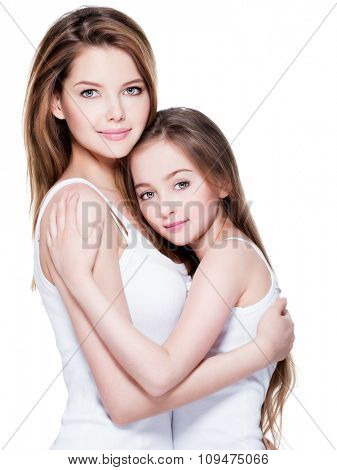 Beautiful young mother with a small daughter 8 years embrace each other at studio
