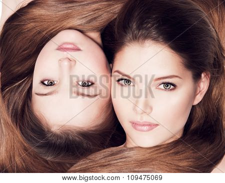Portrait of the beautiful faces of  mother and little daughter 8 years with long hair