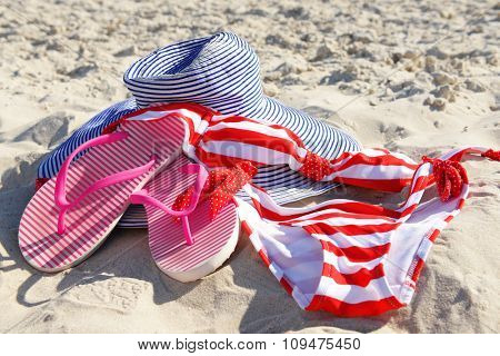Flip flops, swimsuit and hat on beach sand closeup