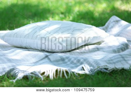 Checked blanket with knitted pillow on green grass in the park