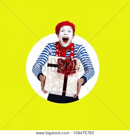 Surprised mime with gift.Funny actor in red beret, sailor suit poses on color background