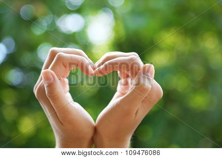 Hands in shape of love heart on nature background