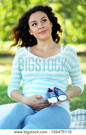 Cute happy pregnant woman with blue booties on white blanket in the park