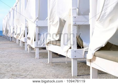 White wooden sunbeds on the beach, close up