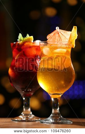 Glasses of cocktail on dark blurred lights background