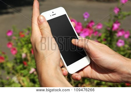 Female hands holding smart mobile phone outdoors