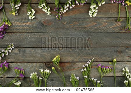 Beautiful wild flowers on wooden background