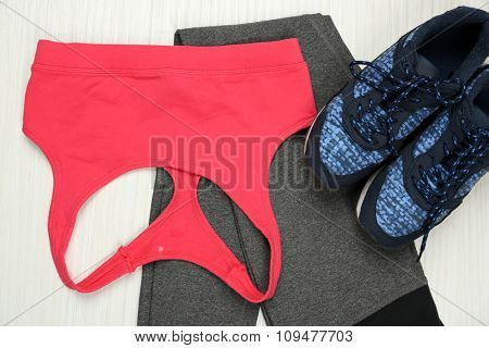 Sport clothes, shoes on light background