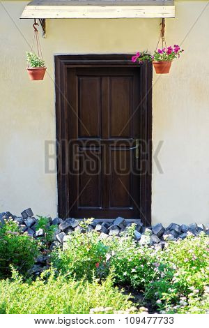 Wooden door with flowers in pots outdoors