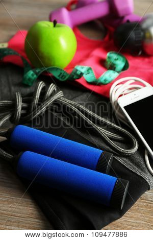 Set for sports and smart phone with headphones on wooden table background