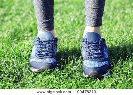 Sports woman legs in sneakers outdoor