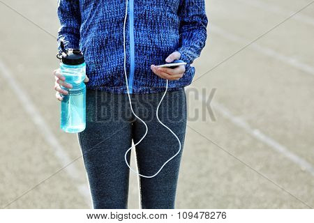 Woman in sports clothes and sneakers with cellphone and bottle
