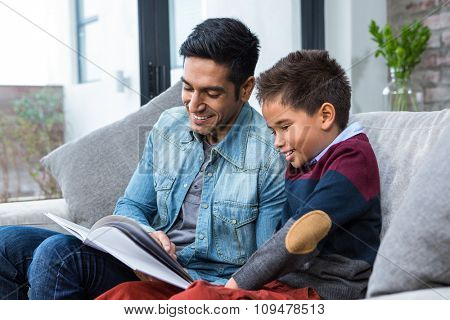 Happy father reading book with his son in living room