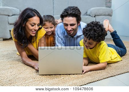 Smiling family using laptop in living room laying on carpet