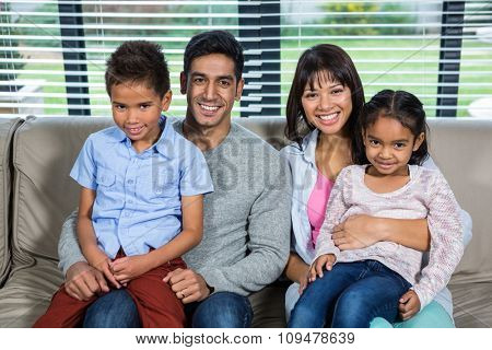 Smiling family on the sofa posing for camera