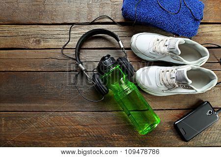 Headphones and sport equipment on old wooden background