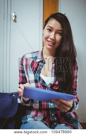Smiling student sitting and using tablet at the university