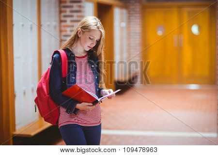Pretty student with backpack holding notebook at the university