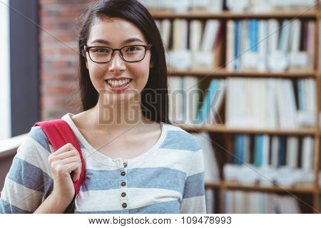 Smiling student with backpack standing in library at the university