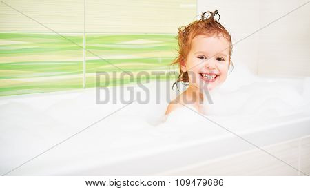 Happy Child Girl Bathes In  Bath With Foam And Bubbles